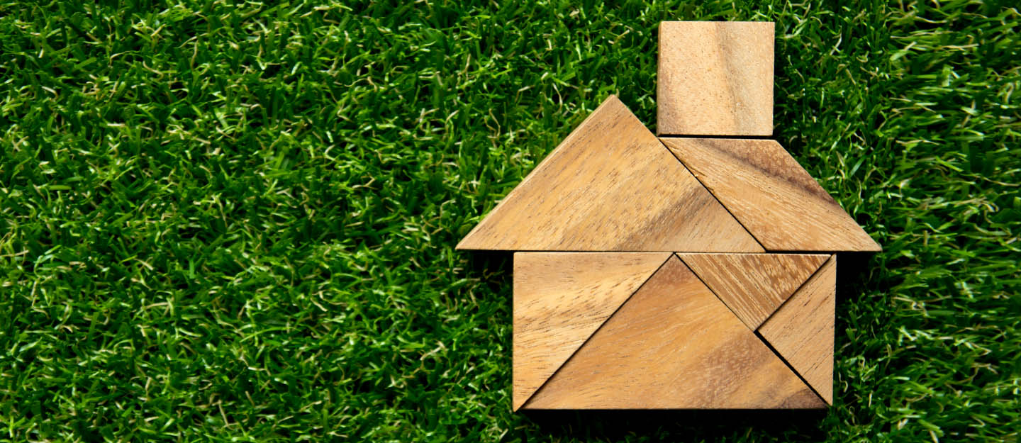 wooden home shape puzzle on green grass background