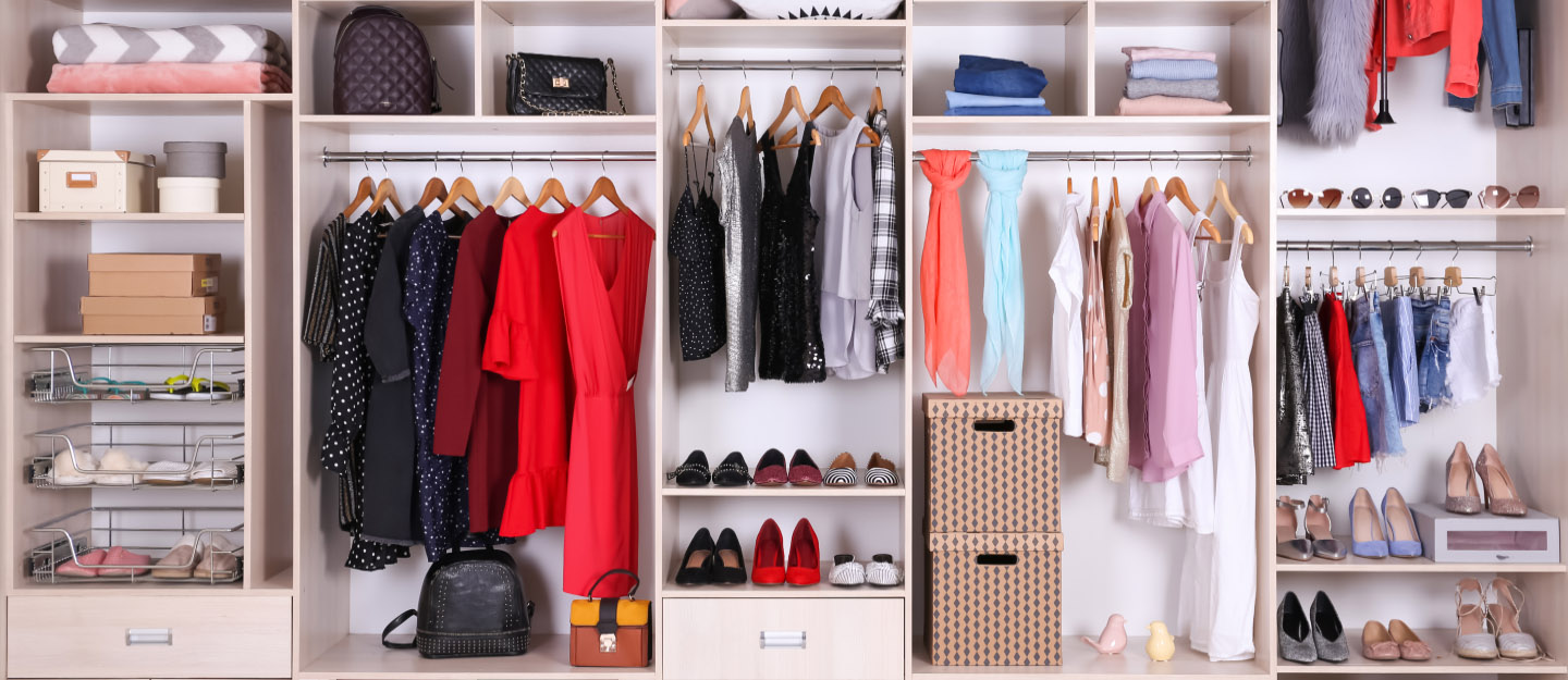 Organized wardrobe with different clothes, shoes, boxes and accessories