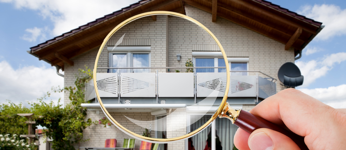 Person holds magnifying glass over a house to symbolize property inspection