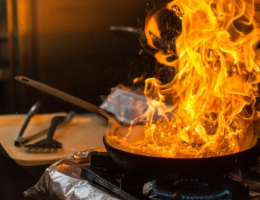 A cooking pan on fire in kitchen