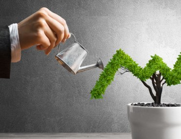 A woman watering a plant shaped as growth graph
