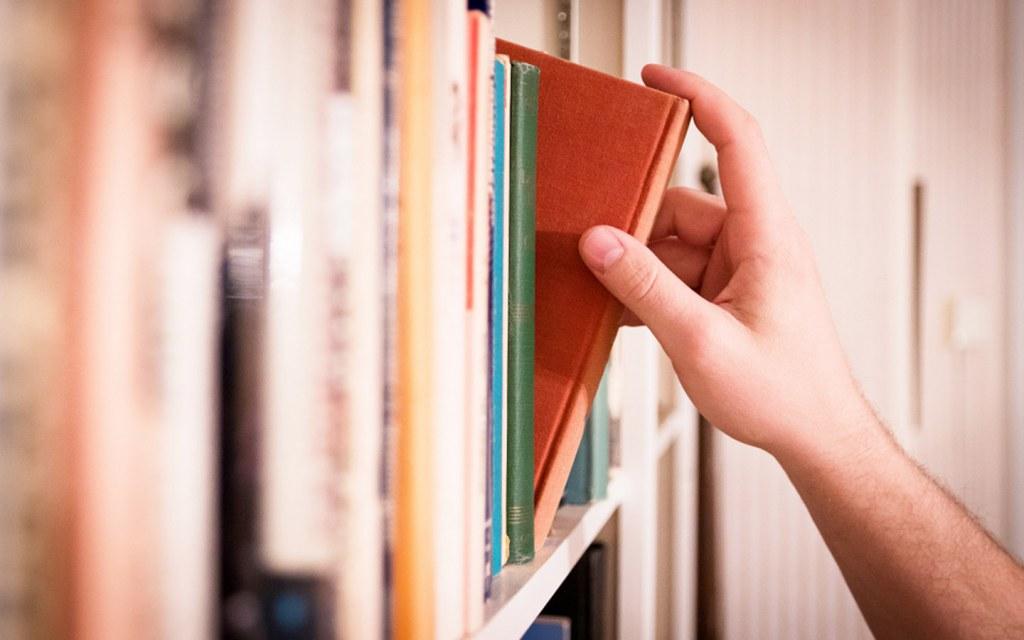 Man picking a Islamic book from shelf