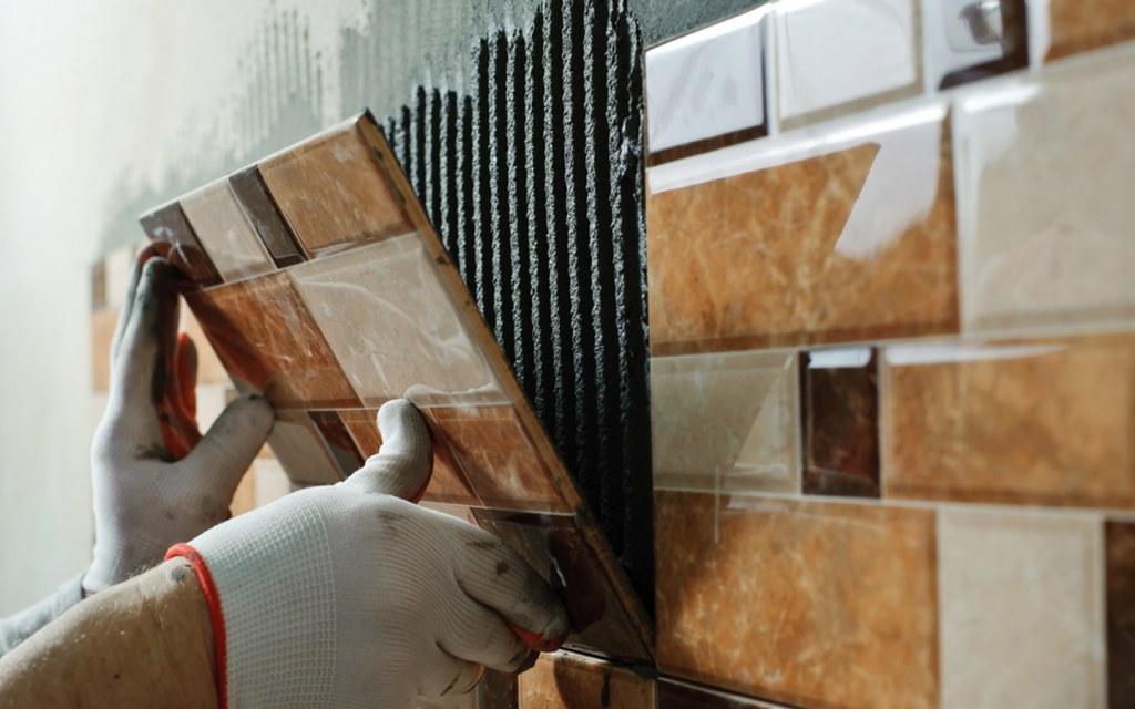 Man installing ceramic tiles on bathroom walls