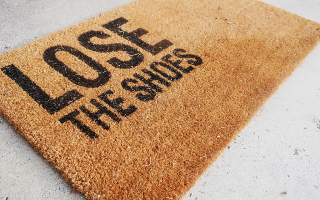 "Rug that reads ""lose the shoes"""
