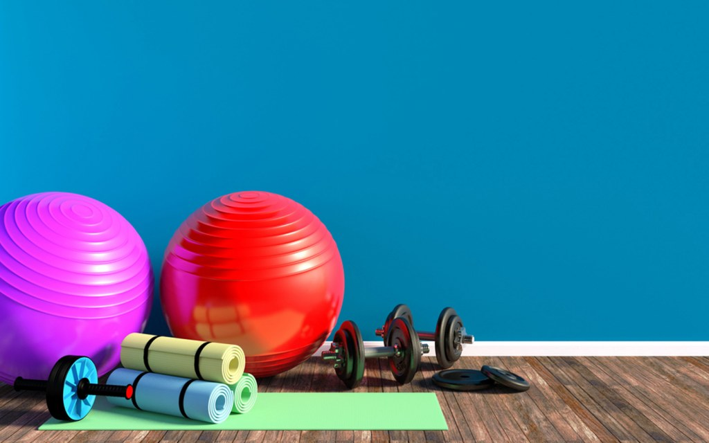 Dumbbells, gym balls, gym weights,and yoga mat on floor