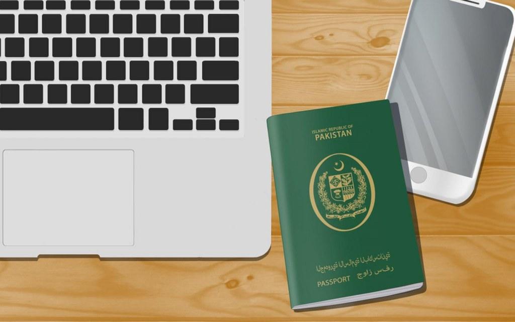 Pakistani passport near mobile and laptop