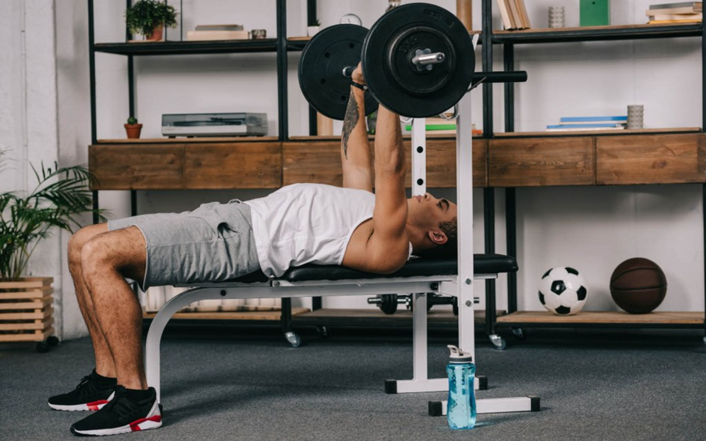 Man on weight bench lifting gym weights