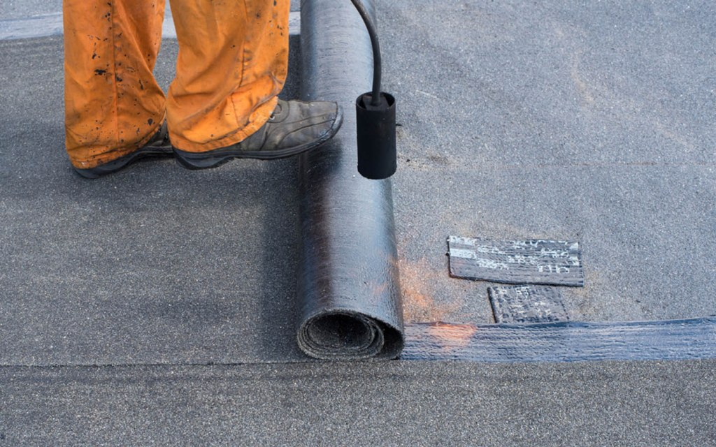 torch-applied bitumen membrane being laid on the rooftop